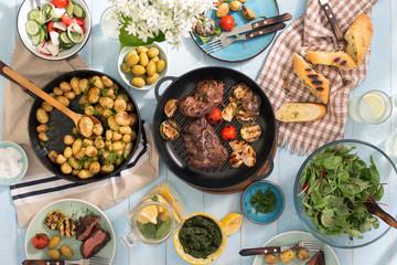 Dinner table with grilled steak, vegetables, potatoes, salad, snacks, lemonade