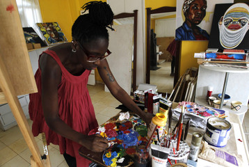 Kenyan artist Awuondo mixes her paints as she works on a creation on a wooden board inside her studio in Gigiri Nairobi