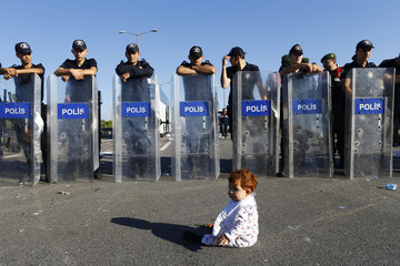 An infant sits on the road in front of a line of Turkish police who block migrants on a highway near Edirne