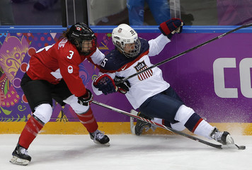 Canada's Larocque and Team USA's Carpenter fight for the puck during the second period of the women's ice hockey gold medal game at the 2014 Sochi Winter Olympic Games