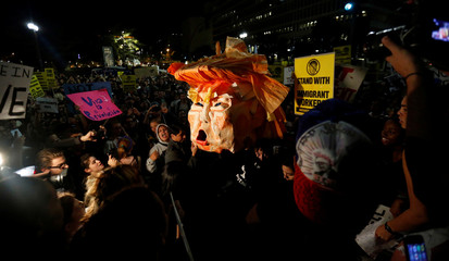 People hold a pinata while protesting the election of Republican Donald Trump as the president of the United States in downtown Los Angeles
