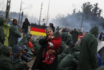 Woman holds child as migrants protest in a makeshift camp on the Greek-Macedonian border near the village of Idomeni