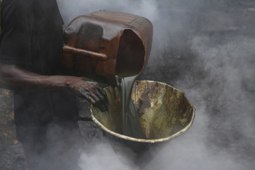 A man pours crude oil into a funnel enveloped by steam at an illegal oil refinery site near river Nun