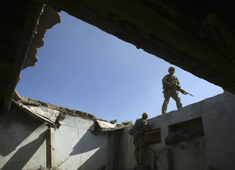 A U.S. soldier of B Troop, 1st squadron of 4th US Cavalry Regiment walks on top of an Afghan police base in the town of Sar Howza in Paktika province
