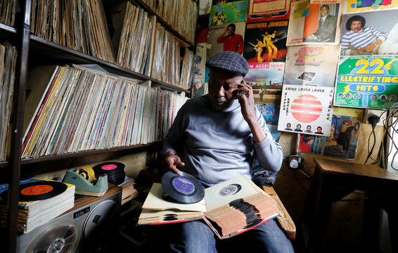 Vendor Rugami looks at a seven inch vinyl records album inside his second-hand vinyl record stalls at the Kenyatta Market in Nairobi, Kenya