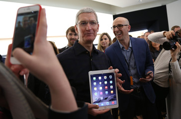 Apple CEO Tim Cook holds a new iPad after a presentation at Apple headquarters in Cupertino
