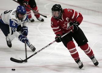Wickenheiser of Canada controls the puck in front of Tuominen of Finland during their semi-final game at the IIHF Ice Hockey Women's World Championship in Burlington, Vermont