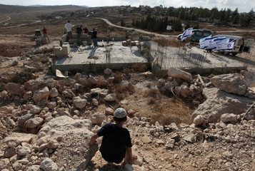 A young boy looks at the construction of a structure on the West Bank Jewish settlement near Hebron