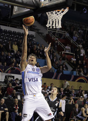 Argentina's Delfino scores as Uruguay's Martinez looks on during their first round match of the FIBA Americas Championship in Mar del Plata