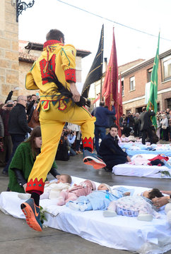 """A man dressed in a red and yellow costume representing the devil and know as """"El Colacho"""" jumps over babies in Castrillo de Murcia"""
