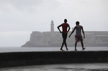 Youths walk in the rain on Havana's seafront boulevard El Malecon