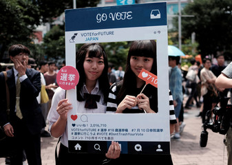 High school students pose for photos with a cardboard Instagram frame calling on youths to vote in the July 10 upper house election, in Tokyo