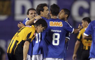 Ribeiro of Cruzeiro celebrates his goal teammates as Filippini of Guarani walks past during their Copa Libertadores soccer match in Asuncion