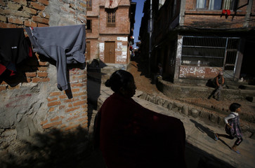 A woman is silhouetted as she walks along a street in the ancient city of Bhaktapur