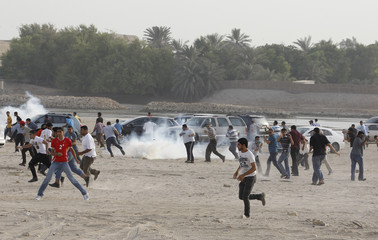 Anti-government protesters run for cover as tear-gas is seen during their attempt to protest at the area where Bahrain's main opposition party Al Wefaq planned to held their anti-government rally in village of Karrana east of Manama