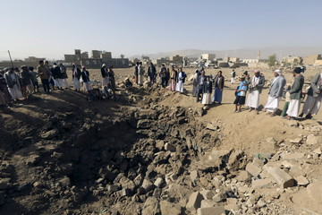 People gather around a crater cause by an air strike in Amran province