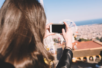 Young woman takes picture with a cell phone