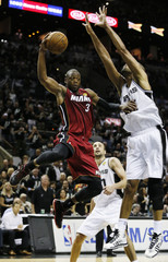 Heat's Wade drives to the net on Spurs' Duncan during Game 3 of their NBA Finals basketball playoff in San Antonio