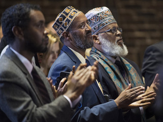 Minneapolis city council member Warsame Imam Adam and Imam Roble, applauds as Democratic presidential candidate Clinton talks during a campaign stop in Minneapolis
