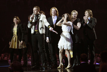 Members of Canadian band Arcade Fire react after winning the International album trophy during the BRIT music awards at the O2 Arena in London