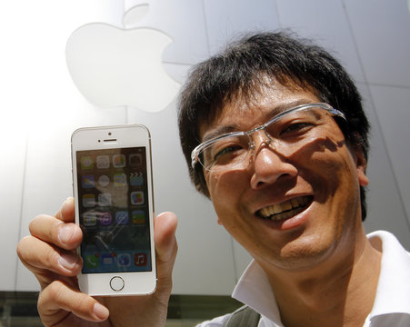 Tetsuya Tamura, who was the first in line, poses with his new Apple iPhone 5S after waiting since September 10, outside an Apple Store at Tokyo's Ginza shopping district