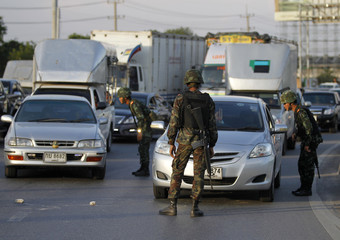 """Armed Thai soldiers block a main road near a pro-government """"red shirt"""" supporters' encampment in Nakhon Pathom province"""