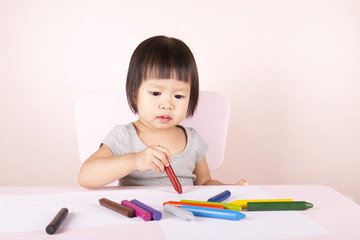 Adorable child drawing with colorful crayons and smiling, with the copy space.