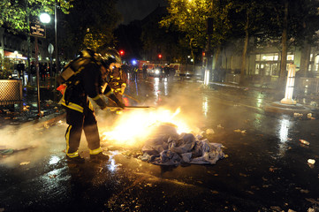 Firemen extinguish medical clothes which were set on fire after police clashed with anaesthetists in Paris