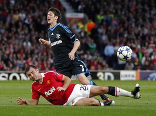 Manchester United's Darron Gibson challenges Schalke 04's Hans Sarpei during their Champions League semi-final second leg soccer match in Manchester.