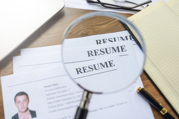 Resume, pen, magnifier, laptop on your desktop. job search