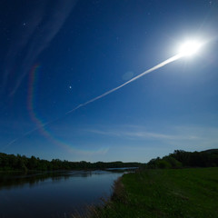Bright full moon in the starry night sky over the river, forest and field.