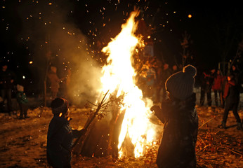 Children throw oak in the burning Yule logs in front of Church of the Holy Prophet Elijah during the eve of the Orthodox Christmas in Sokolac
