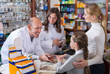 Mother with a girl in the pharmaceutical store