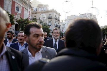 Spain's PM and People's Party (PP) candidate Mariano Rajoy walks along a street during an election campaign in Seville, southern Spain