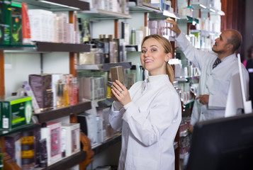 Happy pharmacists standing next to shelves