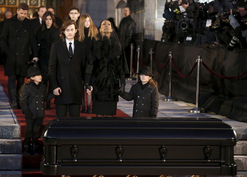Singer Celine Dion looks up to the sky as she stands with her children in front of casket of her husband Rene Angelil following his funeral at Notre Dame Basilica in Montreal