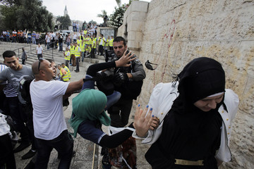 An Israeli border policeman scuffles with a Palestinian woman during clashes at a protest in Jerusalem's Old City