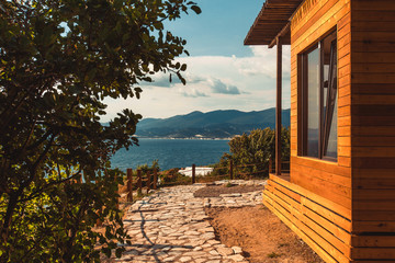 Modern wooden house with  picturesque sea and mountain scenery concept of  vacation by sea