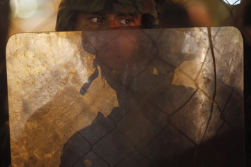A soldier watches a protest rally held by members of the FNRP outside the Presidential House in Tegucigalpa