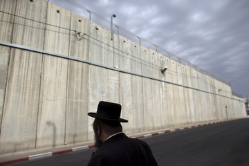 An Ultra-Orthodox Jewish man waits for a bus after visiting Rachel's Tomb in the West Bank town of Bethlehem