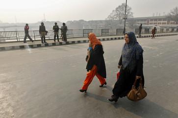 Women walk past Indian policemen guarding an empty road during a curfew in Srinagar