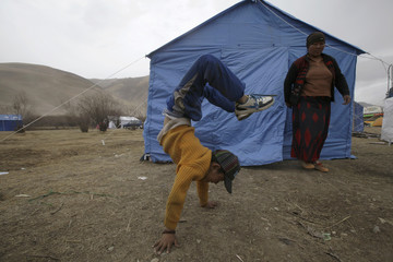 An ethnic Tibetan boy performs a hand stand in front of a tent after his house was destroyed during the earthquake in Gyegu town
