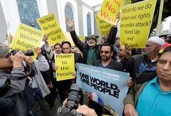 People hold signs after attending Friday prayers at the Islamic Center of Southern California in Los Angeles