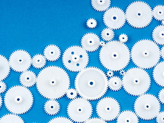 White plastic cogs on blue textured background, with copy space