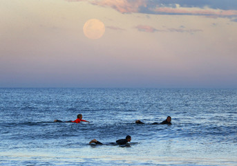 Surfers wait for waves as supermoon rises off Sydney beachside suburb of Wanda