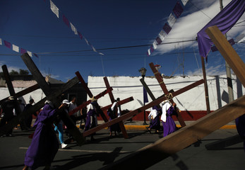 Penitents carry crosses during a re-enactment of the crucifixion of Jesus Christ on Good Friday in Iztapalapa in Mexico City