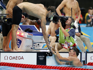 Michael Phelps (L) of the U.S. congratulates his team mate Ryan Lochte after their second place finish in the men's 4x100m freestyle relay race during the London 2012 Olympic Games