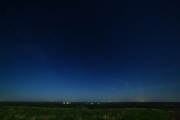 Stars in the night sky with city lights on the horizon. The landscape is photographed by moonlight.