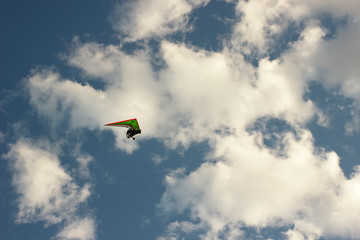 Foto op Aluminium Luchtsport The motorized hang glider flying on background blue sky with clouds.