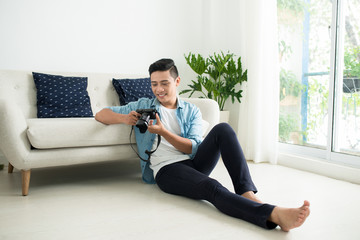 Asian man sitting on the floor and looking at camera near the window at home.